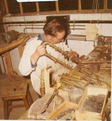 a craftsman is working on a contrabass clarinet.